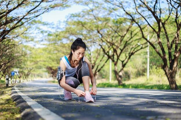 Donna sportiva che lega i lacci delle scarpe mentre ascolta la musica con gli auricolari dal suo smartphone