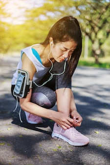 Donna sportiva che lega i lacci delle scarpe mentre ascolta la musica con gli auricolari dallo smartphone in th