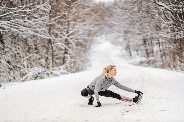 Donna sportiva in abiti sportivi caldi facendo esercizi di stretching al giorno di inverno nevoso nella natura.