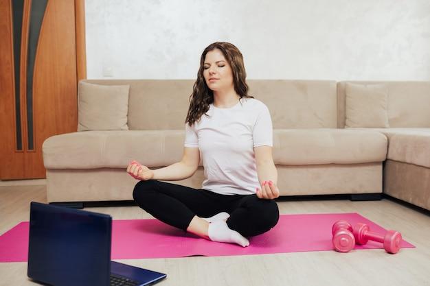 Donna sportiva con gli occhi chiusi sta meditando seduto a casa