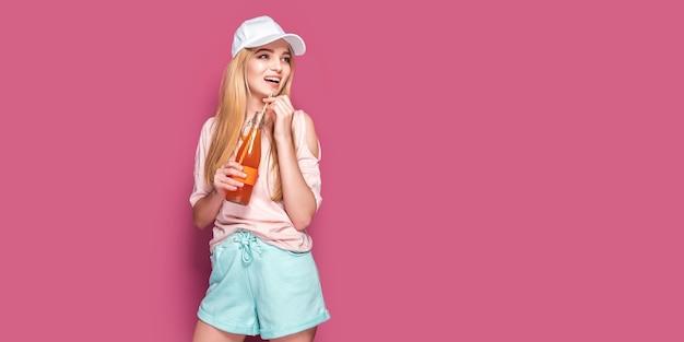 Donna sportiva con bevanda fredda in piedi sulla parete rosa