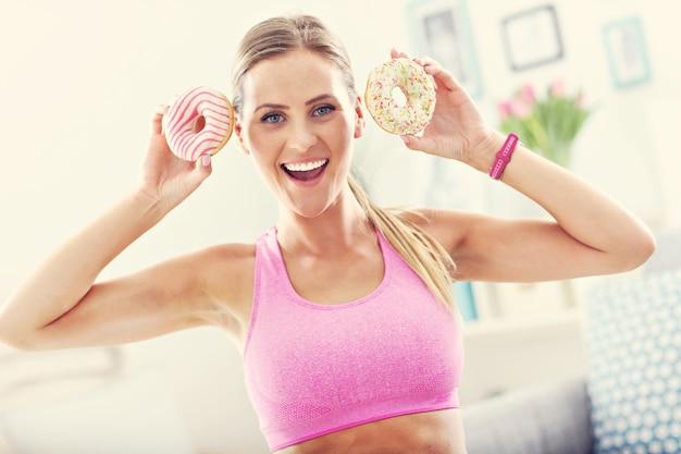 Donna sportiva con ciambelle dopo l'allenamento