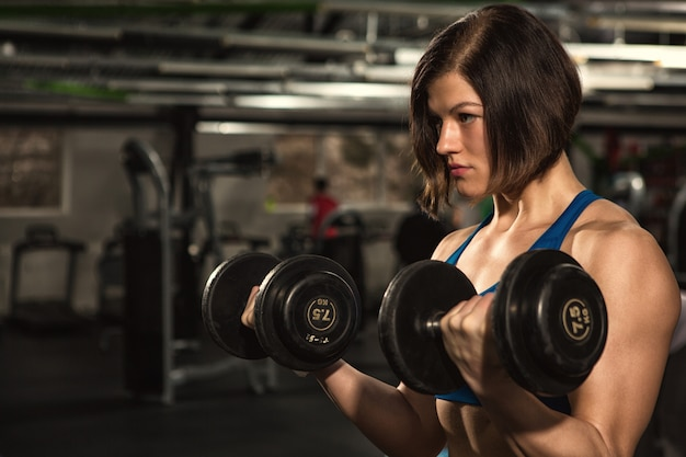 Donna sportiva in manubri di sollevamento dell'ingranaggio di allenamento che risolvono alla palestra