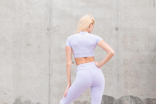 La giovane donna bionda sportiva con un bel corpo snello in abiti sportivi alla moda viola si trova vicino al muro di cemento grigio, vista posteriore