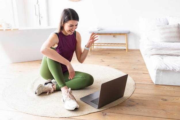 La giovane donna caucasica sportiva seduta sul pavimento a casa usa il laptop per guardare l'allenamento online. concetto di stile di vita sano