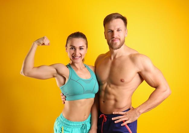 Giovane coppia sportiva su sfondo colorato