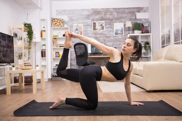 Giovane donna sportiva che fa posa di yoga dell'equilibrio che si siede sulla stuoia a casa.