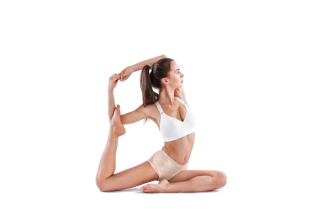 Giovane donna sportiva che fa pratica di yoga isolata su priorità bassa bianca. concetto di vita sana. lunghezza intera.