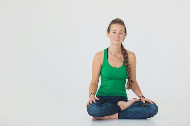 Giovane donna sportiva che fa pratica yoga isolata su priorità bassa bianca - il concetto di vita sana e l'equilibrio naturale tra il corpo e lo sviluppo mentale