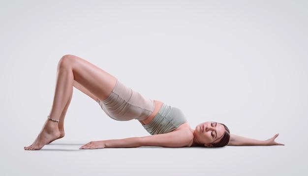 Giovane donna sportiva che fa pratica di yoga. si sdraia sul tappetino e allunga la parte bassa della schiena. isolato su uno sfondo bianco. tecnica mista