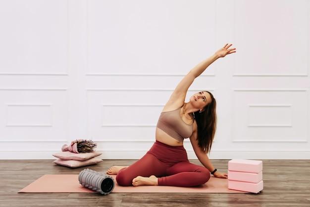 Giovane donna sportiva che fa pratica yoga su priorità bassa bianca