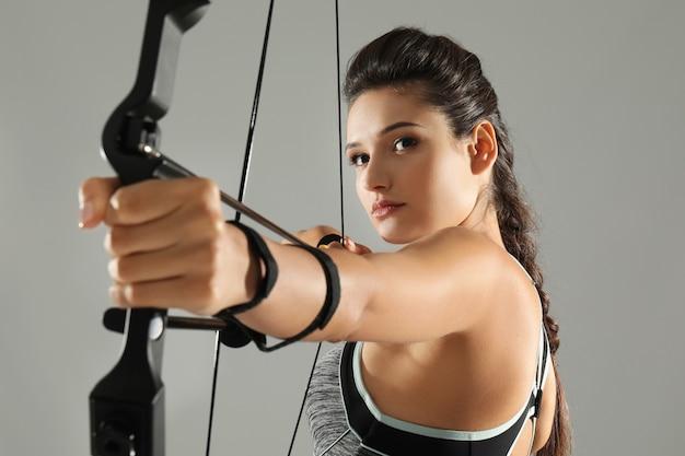 Giovane donna sportiva che pratica tiro con l'arco su sfondo grigio
