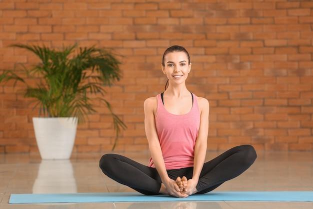 Giovane donna sportiva che pratica yoga a casa