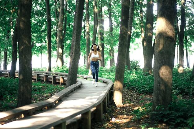 Giovane donna sportiva che corre lungo un sentiero nel bosco