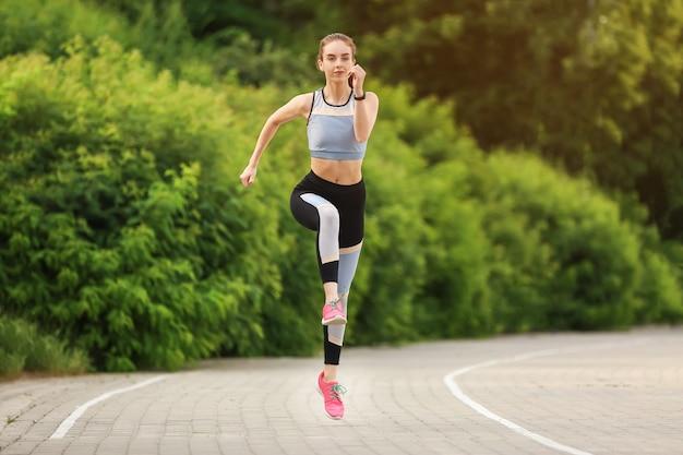 Giovane donna sportiva che funziona nel parco