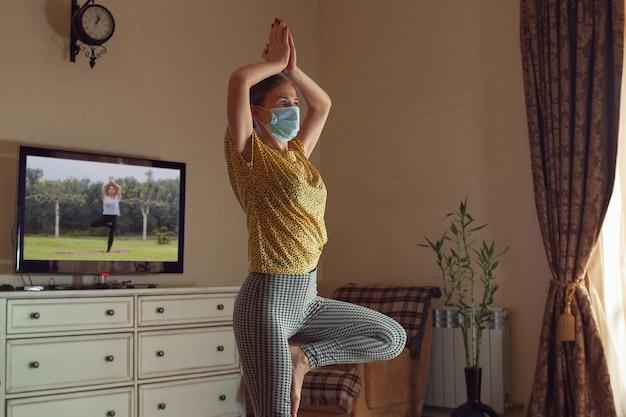 Giovane donna sportiva che prende lezioni di yoga online e si esercita a casa durante la quarantena.
