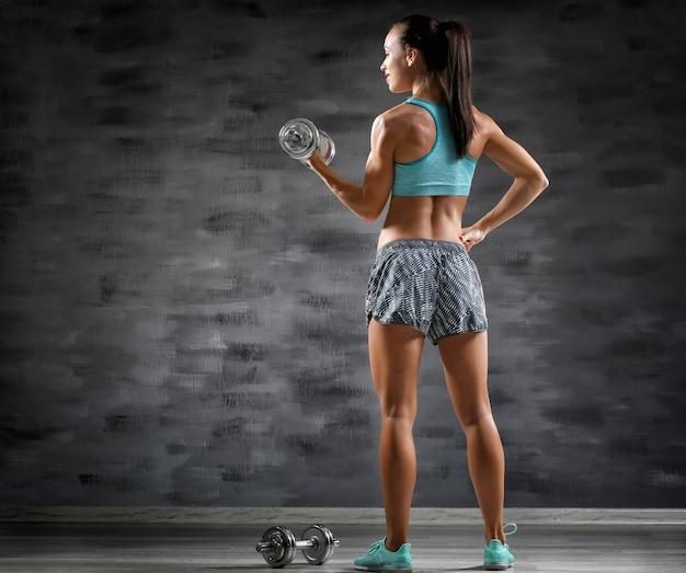 Giovane donna sportiva con manubri su sfondo grigio