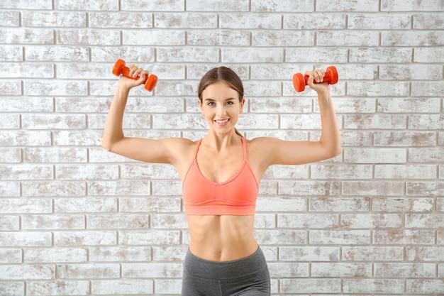 Giovane donna sportiva con manubri vicino al muro di mattoni