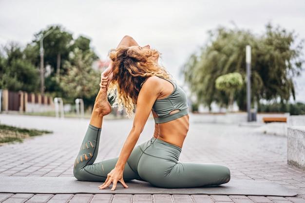 La giovane donna sportiva con capelli lunghi in tuta sportiva grigia che fa l'allungamento si esercita sulla via. stile di vita attivo, concetto di yoga