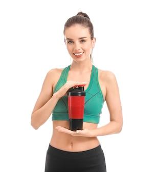Giovane donna sportiva con frullato di proteine su bianco