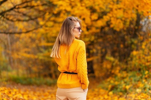 Giovane donna sportiva con gambe snelle sexy in gonna alla moda in eleganti scarpe da ginnastica bianche cammina per strada in giornata di sole. scarpe da donna alla moda. stile estivo. primo piano delle gambe femminili in calzature sportive.