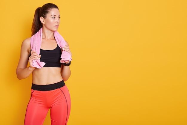 Donna piccante con un asciugamano rosa sulla spalla, in posa isolato su giallo, signora guarda da parte, copia spazio per la pubblicità. fitness, concetto di sport