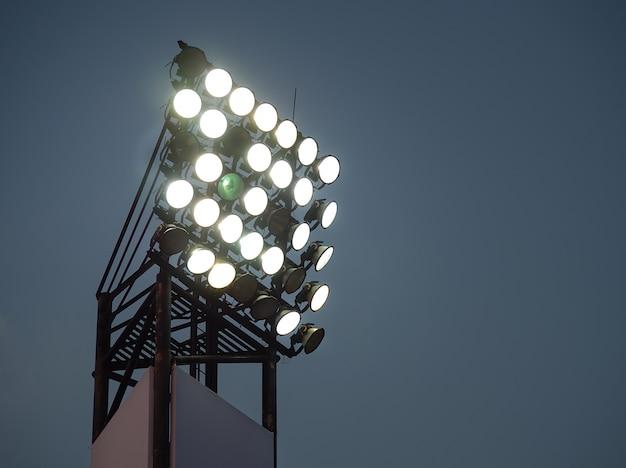 Torri di riflettori sullo stadio notturno o sul parco pubblico. faretto ad alta tensione torre nella notte oscura.