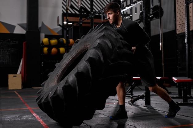 Spotsman spingendo pneumatico tirato per costruire la forza nel moderno centro fitness. il maschio in abbigliamento sportivo è impegnato in cross fit e allenamento. sport, stile di vita sano, bodybuilding, crossfit, concetto di allenamento