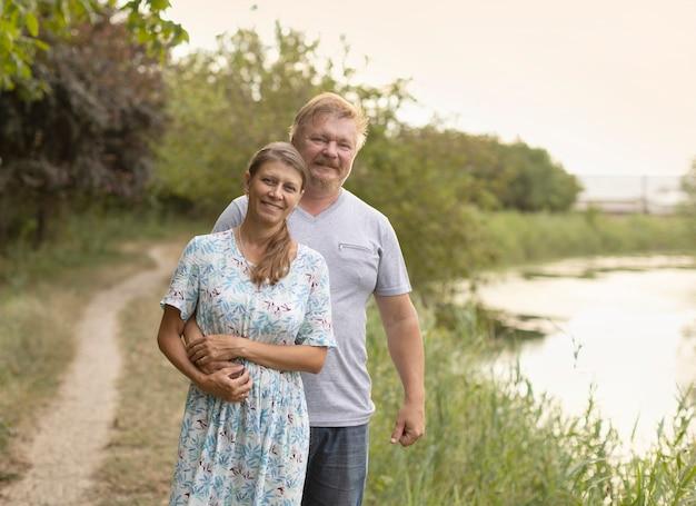 Gli sposi stanno insieme sulla riva del fiume