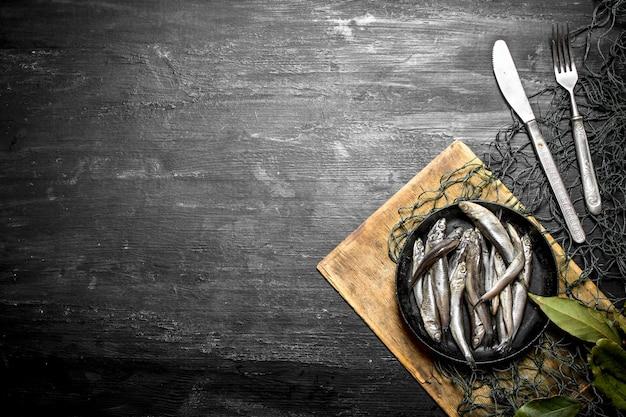 Spratto foglia di alloro in una rete da pesca. su uno sfondo di legno nero.