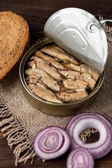 Spratti in un barattolo di latta e pane sulla tavola di legno