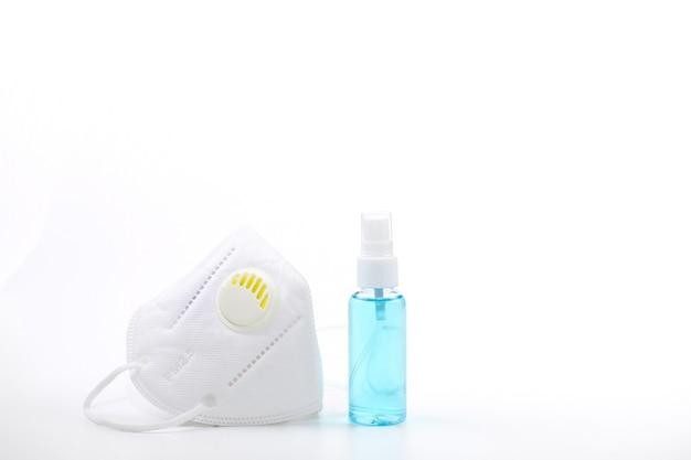 Spruzzare alcol e maschera medica su sfondo bianco che sono respiratori.
