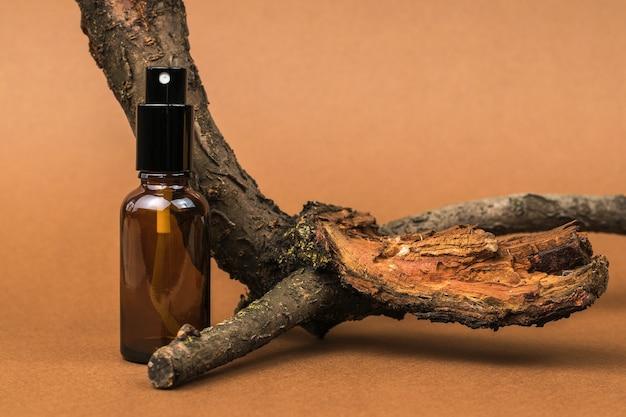 Un flacone spray e un vecchio albero su uno sfondo marrone. cosmetici e medicinali a base di minerali naturali.