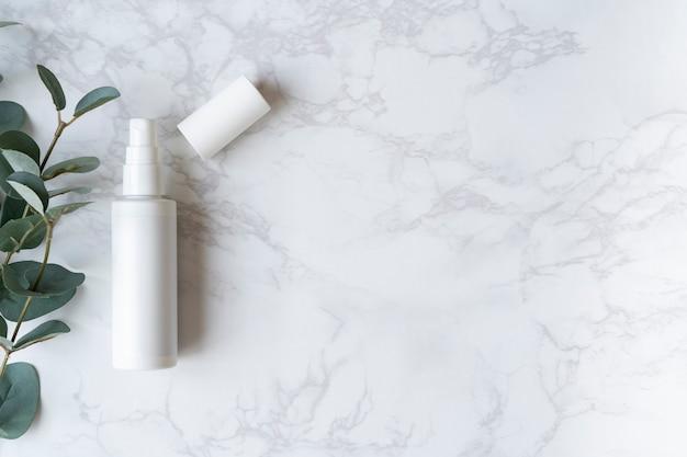 Flacone spray posizionato su una lastra di marmo (lato sinistro dello schermo)