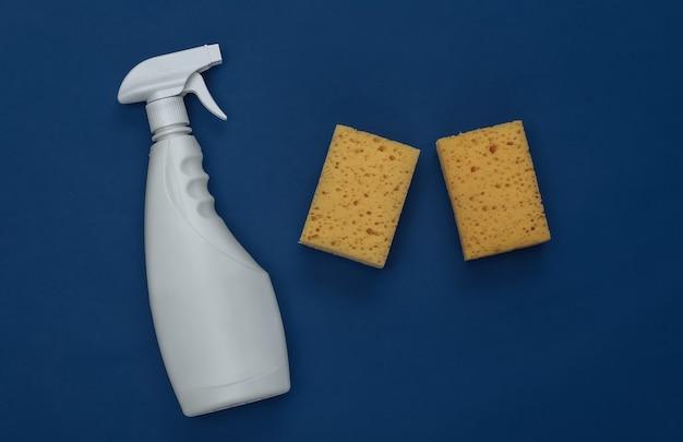Flacone spray e spugne su sfondo blu classico. colore 2020. tema per la pulizia della casa. vista dall'alto