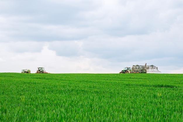 Lo spruzzatore lavora su un campo verde. trattamento del grano con erbicida.