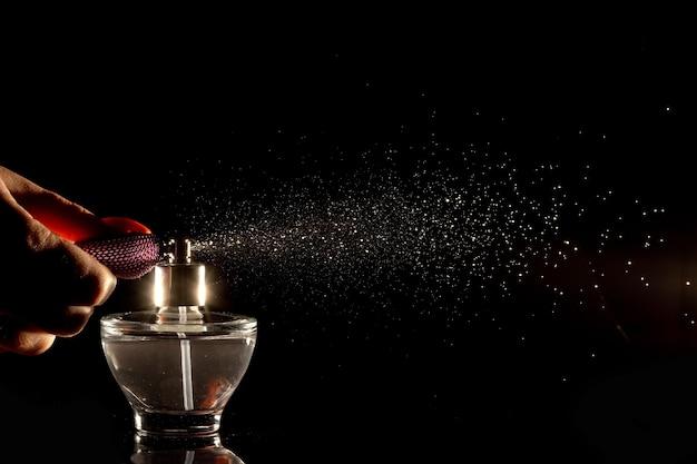 Bottiglia di profumo di spruzzatura di vetro su uno sfondo nero. Foto Premium