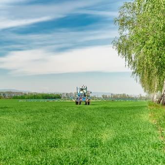 Spruzzando erbacce in un campo da un trattore con uno spruzzatore