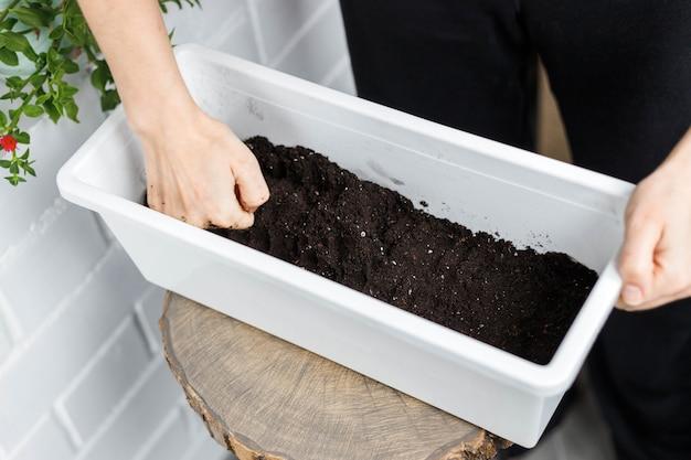 Spargimento del terreno all'interno del vaso da fiori rettangolare bianco