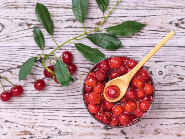 Un rametto di bacche di ciliegia e una ciotola di marmellata di ciliegie su un tavolo di legno