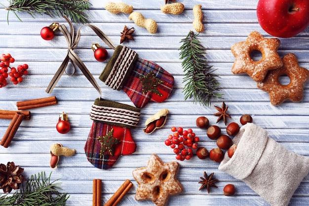 Rametti di albero di natale con biscotti, mele e spezie su fondo in legno colorato