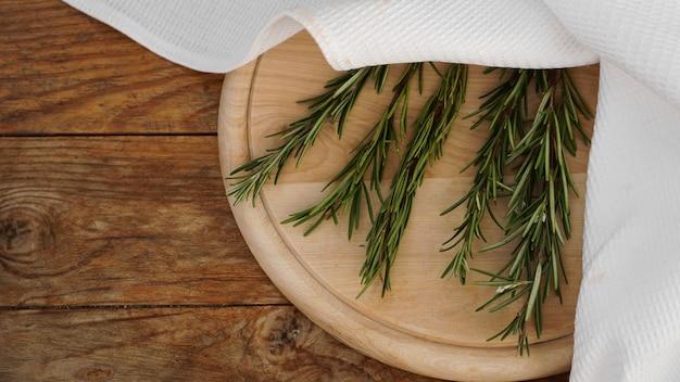 Rametti di rosmarino su una tavola di legno per il taglio. stile rustico. spezia