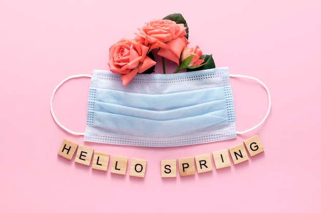 Primavera 2021. concetto covid-19. maschera medica con fiori di primavera su uno sfondo rosa.