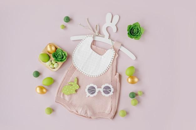 Vestiti primaverili per bambini. body in maglia su simpatico appendiabiti con orecchie da coniglio con decorazioni pasquali e uova su sfondo rosa pallido. concetto di vacanza. disposizione piatta, vista dall'alto