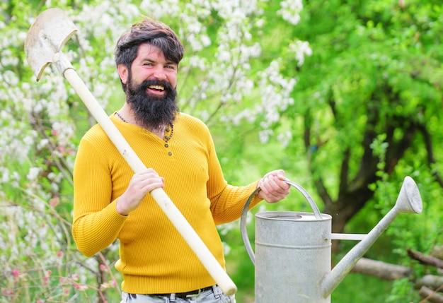 Primavera, giardiniere barbuto con annaffiatoio e vanga, uomo sorridente che si prepara a piantare, contadino che lavora in giardino.