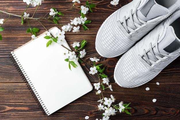Ramo di fiori di primavera, scarpe da ginnastica e taccuino su fondo di legno scuro.
