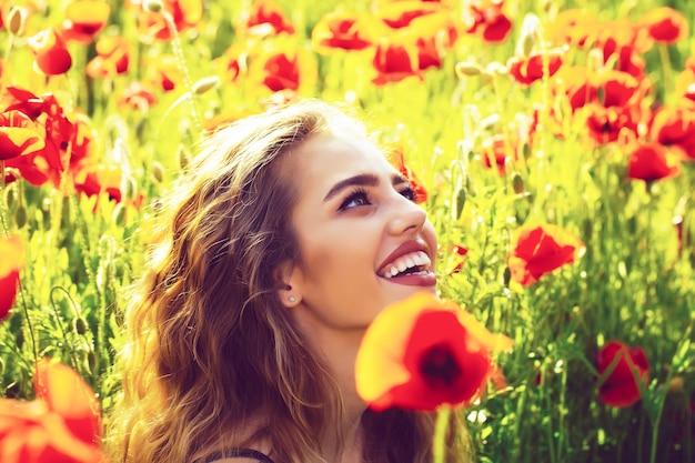 Fiore di primavera. ritratto facciale del modello femminile sexy. bella donna sul campo di papaveri con volto sorridente.