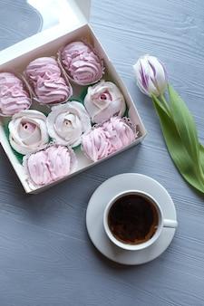 Celebrazione della primavera laici piatta. tazza bianca con caffè, tulipani rosa e marshmallow. sfondo vacanza. biglietto d'auguri.