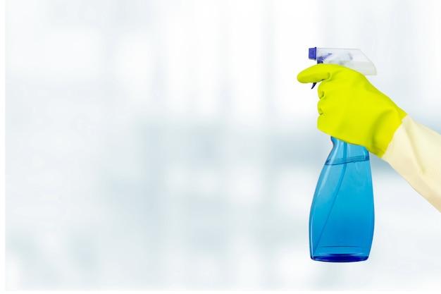 Concetto di pulizie di primavera. mano nel guanto protettivo che tiene il flacone spray per la pulizia. disinfezione o concetto di igiene sull'epidemia di coronavirus.
