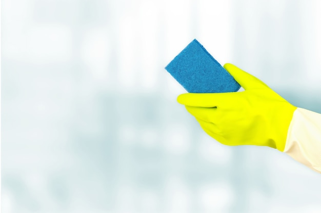 Concetto di pulizie di primavera. vista dall'alto delle mani in guanti di gomma che tengono la spugna su sfondo blu. disinfezione o concetto di igiene sull'epidemia di coronavirus.